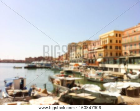 Sea view in European town. Italian coastal city blurred photo. Beach harbor and boats by the sea. Summer town in Italy blurry image for background or postcard. Vintage seaside picture in blur