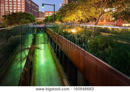 The High Line promenade illuminated at twilight in the West Village. The aerial greenway is also known as Highline or High Line Park. It is a former elevated rail line turned creative urban renewal project. Manhattan New York CIty