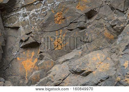 Muddy orange hand prints on a cracked stone wall