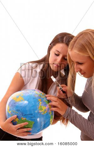 Two happy young girls with globe on white