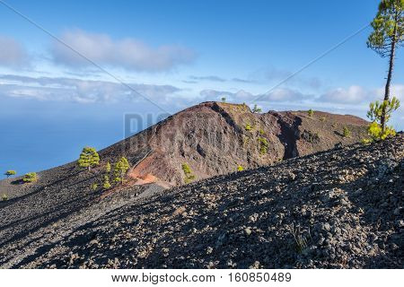 """Shot of the famous hiking path """"Ruta de los vulcanos"""" taken in the south of la Palma nearby Los Canarios. View at the rim of a volcano crater"""