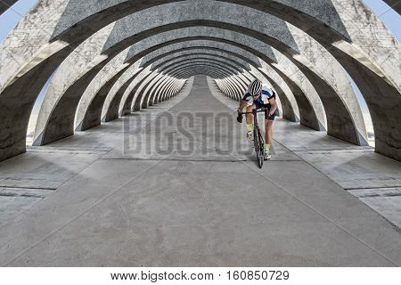 Front view of race biker who rides his bike under floating concrete light flooded arcades.