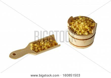 Bucket and shovel with millet from the set of wooden kitchen utensil for children to play isolated on a white background