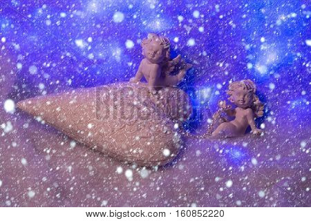 Closeup of beautiful soulful figurine composition of cupid angels for valentine day or christmas with small pillow in shape of heart lying on white wadding decorating snow with bright light sparks