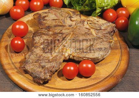 Grilled T bone steak with tomatoes onions and pepper garnished on a rustic wooden chopping board