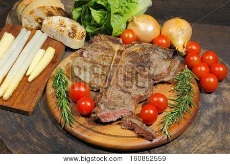 Grilled T bone steak with rosemary tomatoes corn onions and asparagus garnished on a rustic wooden chopping board