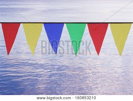 Multi Colored Triangular Flags Hanging in the Sky at an Outdoor on the background of blue water