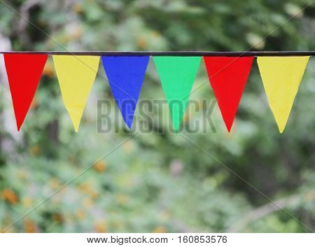 Multi Colored Triangular Flags Hanging in the Sky at an Outdoor against the backdrop of a green grass.
