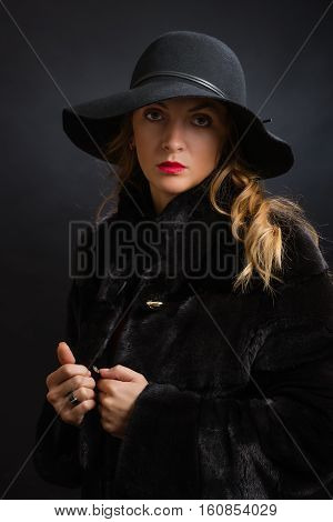 The beautiful young girl in a black hat with wide fields and a fur coat from fur