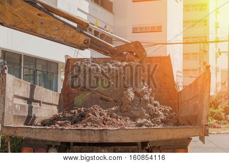 Excavator or soil mud into truck body Work and motion soil mud with sunset light tone.