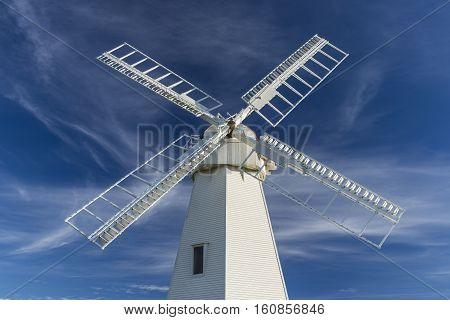 A white windmill against a blue sky with clouds.