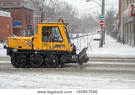 Montreal CA - 5 December 2016: A snowplow in motion on Mont-Royal Avenue during snow storm.