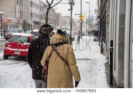 Montreal CA - 5 December 2016: Snowstorm in Montreal. Pedestrians on Mont-Royal Avenue.