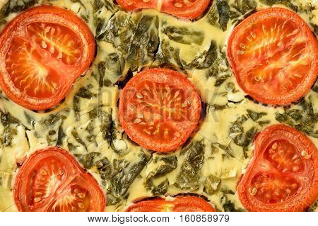 Homemade quiche with spinach, feta cheese and tomatoes.