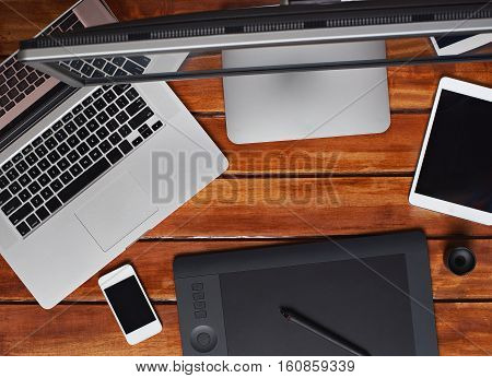 working space of retoucher on wooden table with gadgets computer, screen , smartphone and tablet