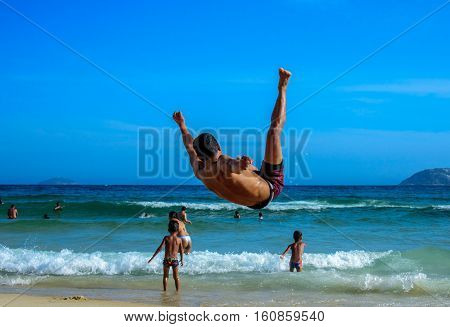 Back of the flying man performing somersault at Ipanema Beach and backs of swimming children and adults in Atlantic Ocean at sunny day, Rio de Janeiro, Brazil
