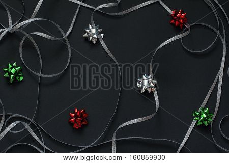 Pattern swirls of silver ribbon and bows for gifts green, red and silver colors. Christmas/New Year decorations  Black background, top view, flat lay