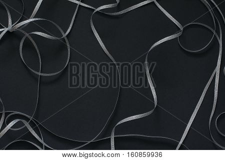 Frame with silver ribbon scrollwork. Decor for celebration. Black background, top view, flat lay, copy space