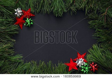 Frame of pine branches decorated with red stars of felt and bows of red, green and silver color. Christmas/New Year decorations Black background, top view, flat lay, copy space