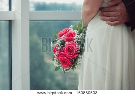 bride in a white dress hugs her husband, she was standing at the window, without a face