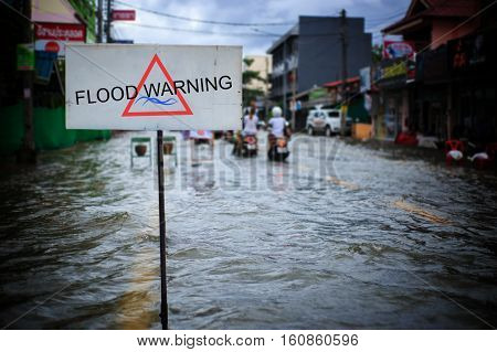 Flooded street after heavy rain. Motorist driving through flood waters with flood warning sign.