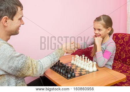 Dad And Daughter Greeted Each Other Hands, About To Play A Game Of Chess