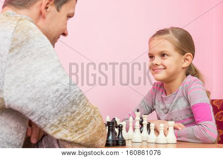 Dad And Daughter Happily Look At Each Other, Playing Chess