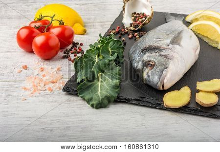 Useful dorado fish, rich in protein, vitamins, Omega 3 with vegetables, lemon and ginger, prepared for cooking on a white wooden table.