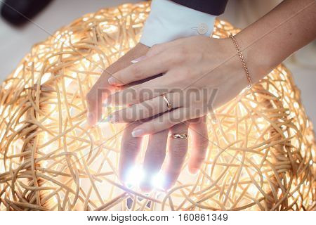 arms couple with rings lit by bright light, gold wedding
