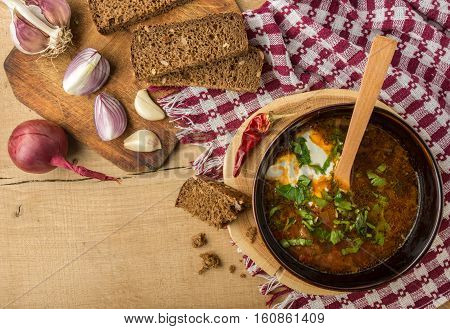 Tasty and nutritious borsch-soup with meat, potatoes, cabbage, tomatoes, beans, sour cream, parsley, onion, garlic, dark bread in a clay plate on a wooden tray and wooden table. Top view
