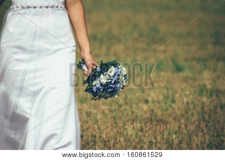 bride in white dress is on the field with a bouquet without a face