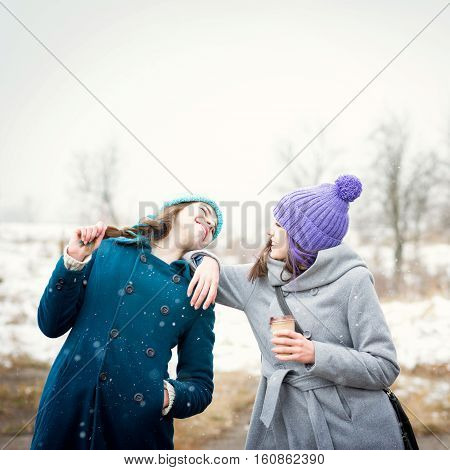 Two teenage girls having fun outdoors on snowy winter day in park. Two female friends enjoying outside in wintertime and laughing.