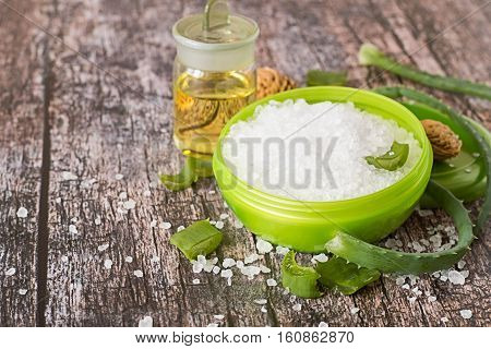 Spa pampering. Round jar with sea salt, leaves of the aloe vera plant and a glass bottle with scented oil on a wooden table.