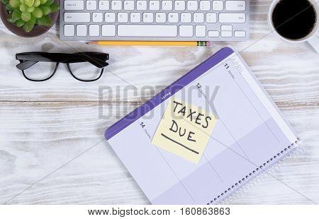 Tax concept with calendar reminder and other desktop work supplies.