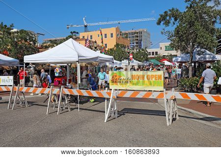SARASOTA, FLORIDA - NOVEMBER 19 2016: Vendors and shoppers at the Sarasota Farmers Market in fall. This vibrant event occurs downtown on Lemon Avenue and State Street every Saturday from 7 AM to 1 PM.