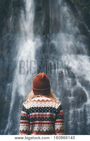 Woman looking at waterfall traveling alone Travel Lifestyle adventure concept vacations into the wild wearing cozy sweater and hat
