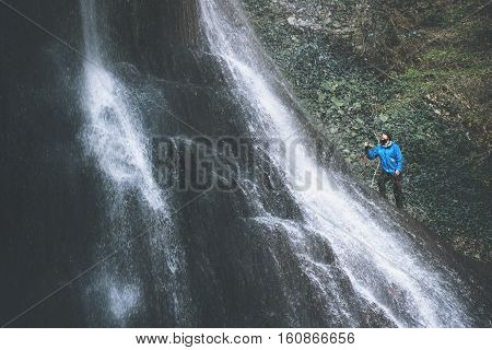 Man Traveler climbing on waterfall rocks Travel Lifestyle adventure concept extreme vacations survival into the wild