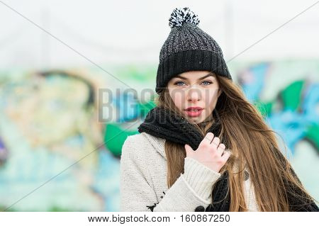 Young woman in black knit beanie and scarf outdoors in winter. Gorgeous teenage girl in coat and knit black hat posing on cold winter day. Copy space, medium retouch, natural light.