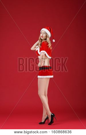 sexy woman blonde in the clothes of Santa Claus on a red background.