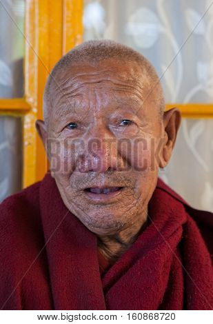 DHARAMSALA, INDIA. 2 Jun 2009: Daily lifestyle of the monks in a Buddhist monastery.  Closeup portrait of a Buddhist monk.  Residence of His Holiness the Dalai Lama XIV. McLeod Ganj, Western Himalayas, Himachal Pradesh, district of Kangra.