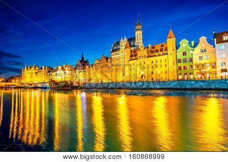 Night view on the illuminated riverside with beautiful buildings of the old town in Gdansk, Poland