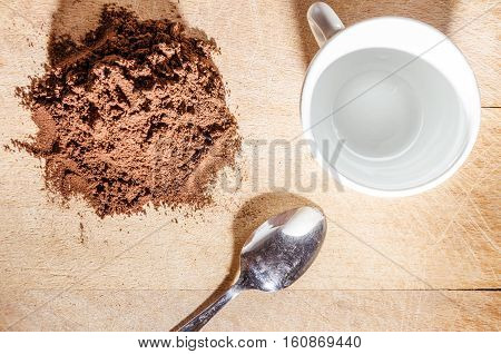 stille life with a white cup and stell little spoon beside a pile of coffe powder