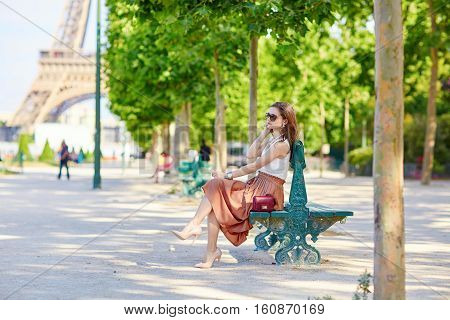 Beautiful Young Parisian Woman Sitting On The Bench
