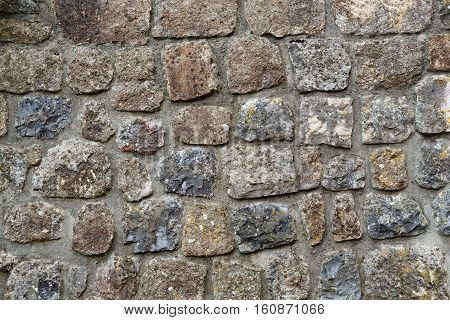 Texture of gray stone wall covered with lichen