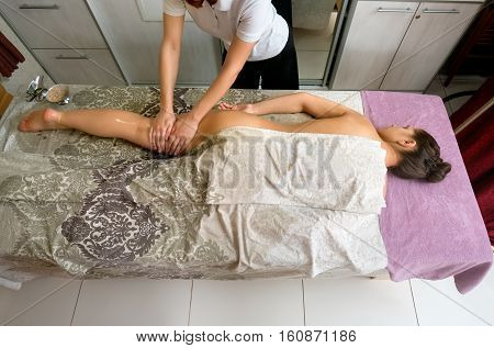 Top view of beautiful woman lying on massage table, therapist massaging her body. Young girl getting spa treatment. Beauty and helth care concept