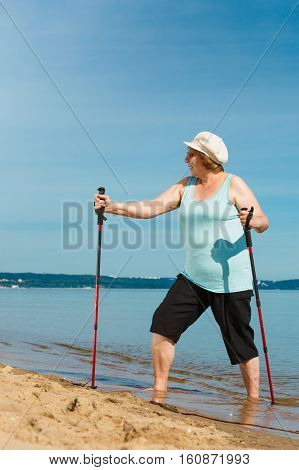 Senior woman practicing nordic walking on sea shore Active elderly female enjoying sunny summer day. Healthy lifestyle in old age.