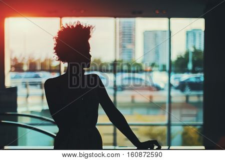 Silhouette of young black curly Brazilian girl in front of window standing in supermarket and talking on the phone with blurred escalator behind her and cityscape out of the window