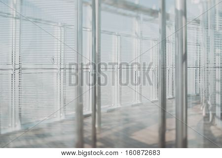 Abstract white office interior background the sun rays glass chrome columns and blinds view from skyscraper through the window the Dubai cityscape outside