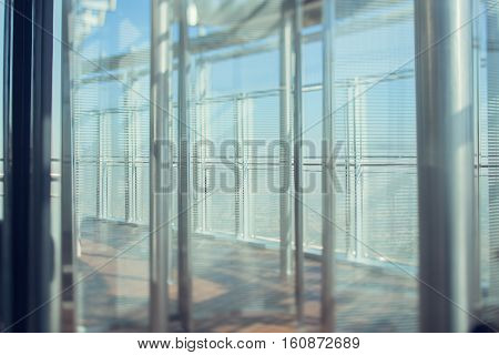 Abstract bright office interior background the sun rays glass chrome columns and blinds view from skyscraper through the window the Dubai cityscape outside