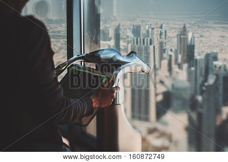 True tilt shift shooting of wrinkly old woman hands using touristic electronic zoom device with black screen and chrome case Dubai cityscape behind the window summer sunny day with haze